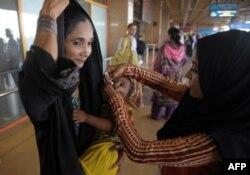 Пәкістандық медицина қызметкері анасының қолындағы сәбиге полиомиелит ауруына қарсы дәрі тамызып жатыр. Карачи әуежайы, Пәкістан, 7 мамыр 2014 жыл.
