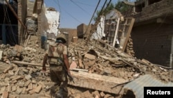 File photo of a Pakistani soldier walking inside destroyed house in North Waziristan in July.