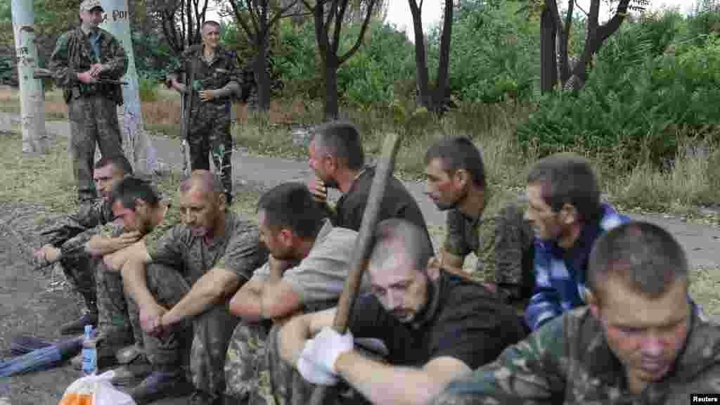 Пресс-секретарь президента Украины Святослав Цеголко 7 сентября сообщил, что сепаратисты начали отпускать украинских военнослужащих, взятых в заложники. По данным Совета национальной безопасности и обороны Украины, сепаратисты удерживают в заложниках более 200 человек. На фото: пленные украинские военные под надзором вооруженных сепаратистов.