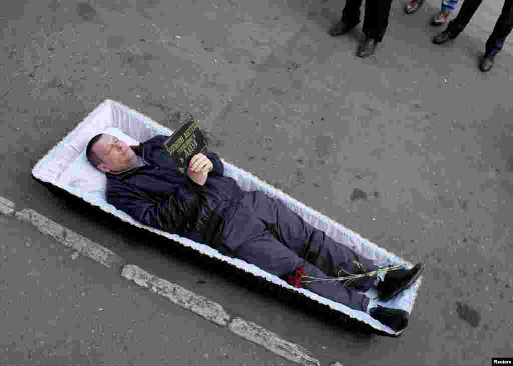"A man lies inside a coffin as activists protest against the sale of medication that they say can be used for the production of synthetic drugs in Pyatigorsk, Russia. The board reads: ""Pharmacy keeper! See you in hell."" (Reuters/Eduard Korniyenko)"