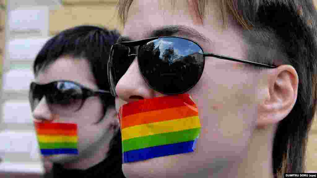 Two Moldovan lesbians cover their mouths during a silent protest in the Moldovan capital, Chisinau, on April 27, 2007, after the authorities banned a public event by an LGBT group.