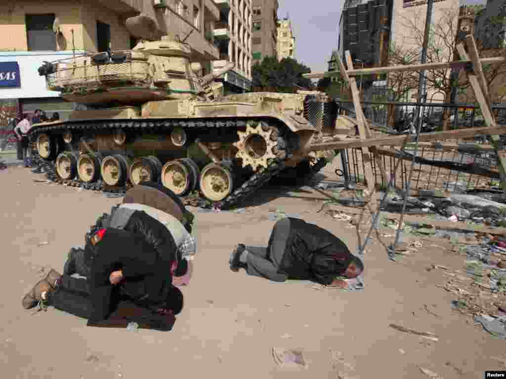 Opposition supporters pray next to a tank on Tahrir Square.