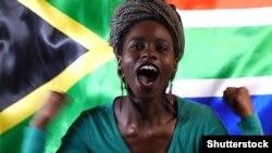 Маладая паўднёваафрыканка на фоне нацыянальгага сьцягу