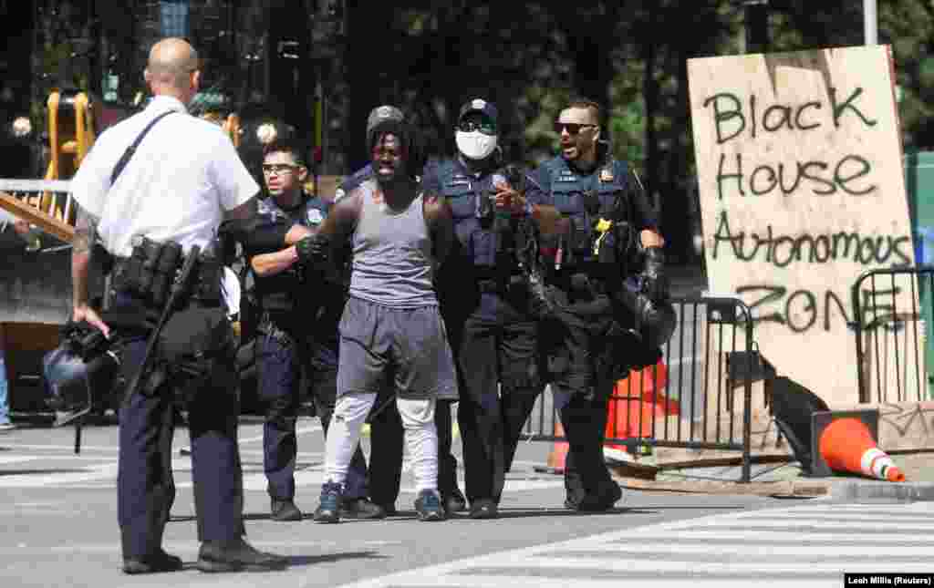Washington, D.C. Metropolitan Police officers detain a man as they clear the entire area around Black Lives Matter Plaza during racial inequality protests near the White House in Washington, U.S., June 23, 2020.