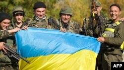 Українські військовослужбовці з прапором на контрольно-пропускному пункті поблизу міста Попасна в Луганській області, 2 жовтня 2014 року