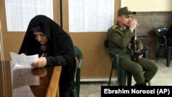 A voter fills out her ballot in the parliamentary elections as a soldier guards a polling station in Tehran, February 21, 2020