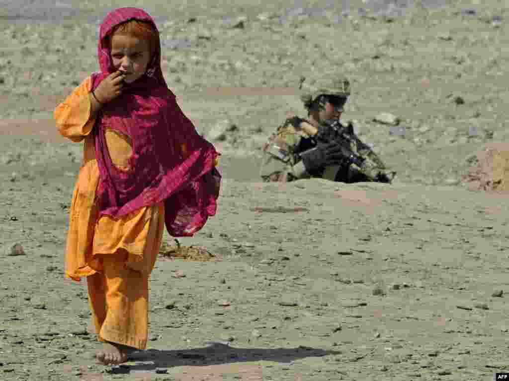 A U.S. Army soldier patrols as a girl walks past in Turkham Nangarhar, bordering Pakistan. (Photo by Tauseef Mustafa for AFP)