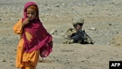 Афганская девочка проходит мимо американского солдата на афганско-пакистанской границе. 3 октября 2011 года.