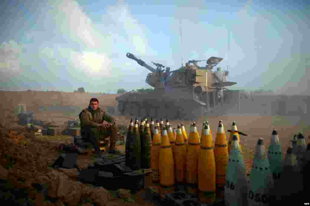 Israeli soldiers rest next to shells from an artillery unit near the Israeli border with Gaza. (epa/Abir Sultan)