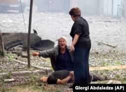 Грузинская женщина плачет у трупа после удара российской авиации в городе Гори, 9 августа, 2008 года