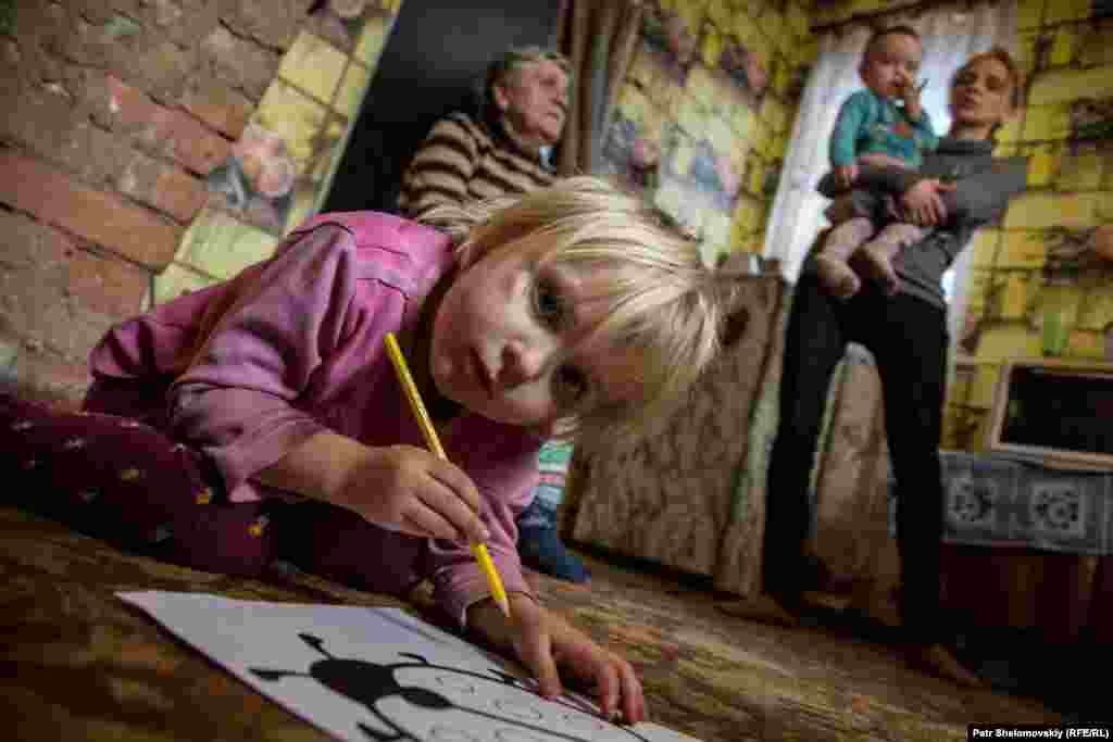 Masha draws pictures at her home in the Petrovskiy district of Donetsk. Her family was among some 40 people, including 19 children, who lived in a bomb shelter for more than a year. In spite of the cease-fire agreement that went into force in February 2015, sporadic bombing and shelling have continued, and residents are still afraid to sleep in their own homes at night.