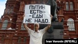"""Активист Владимир Ионов во время одиночного пикета держит плакат с надписью: """"Путин есть - еды не надо"""". Москва, 15 августа 2015 года."""
