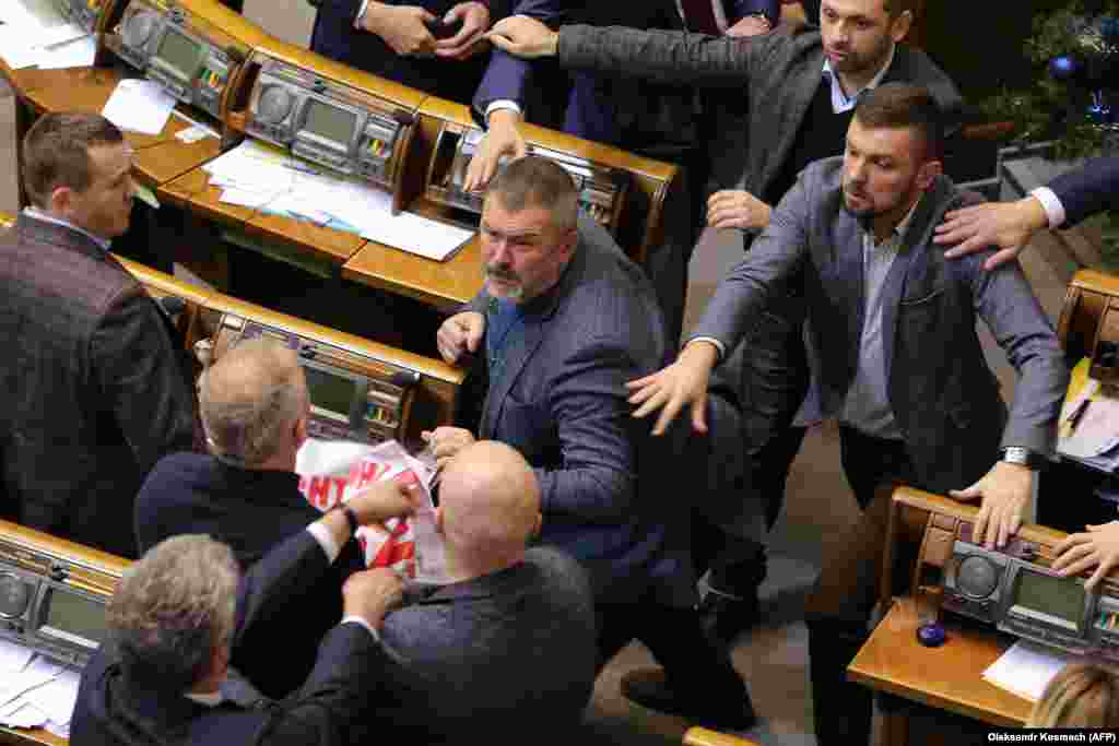Ukrainian members of parliament scuffle during a session in Kyiv on December 20. (AFP/Oleksandr Kosmach)