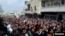 Thousands of people attend a mass funeral for pro-democracy protesters in the city of Daraa earlier this month. (file photo)