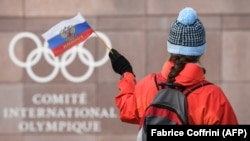 A supporter waves a Russian flag in front of the logo of the International Olympic Committee at their headquarters near Lausanne. (file photo)