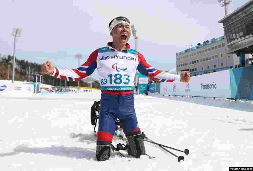 Паралимпийский лыжник из Южной Кореи празднует победу в мужском 7,5-километровом забеге на беговых лыжах
