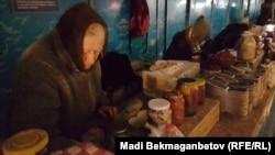 Пожилые люди продают домашние заготовки в Астане. Слева - жительница столицы, представившаяся Лидией Ивановной. 10 ноября 2016 года.