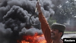 A man shouts antigovernment slogans in front of burning tires during a protest against power cuts in Lahore.