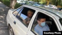 Полицейские увозят активистку Санавар Закирову (на заднем сиденье машины) из дома в СИЗО после обвинительного приговора, по которому она осуждена на год лишения свободы. Алматы, 15 июля 2020 года.