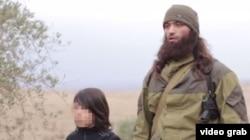Слева – мальчик-боевик, казнивший двух мужчин (лицо мальчика заштриховано). Справа – боевик, руководивший казнью. Кадр пропагандистского видео экстремистской группировки «Исламское государство».