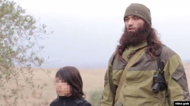 Скриншот видео с мальчиком, предположительно выходцем из Казахстана, который показан в видеоролике как исполнитель казни двух мужчин, якобы внедренных российскими спецслужбами в среду боевиков ИГ.