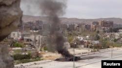 Damaskyň etegindäki transport ýolunda Siriýanyň hökümet güýçlerine degişli bir tank ýanýar. Damask, aprel, 2013.