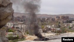 A tank belonging to government forces is set on fire during clashes between government forces and the Free Syrian Army, on the main southern highway near Damascus, on March 19.