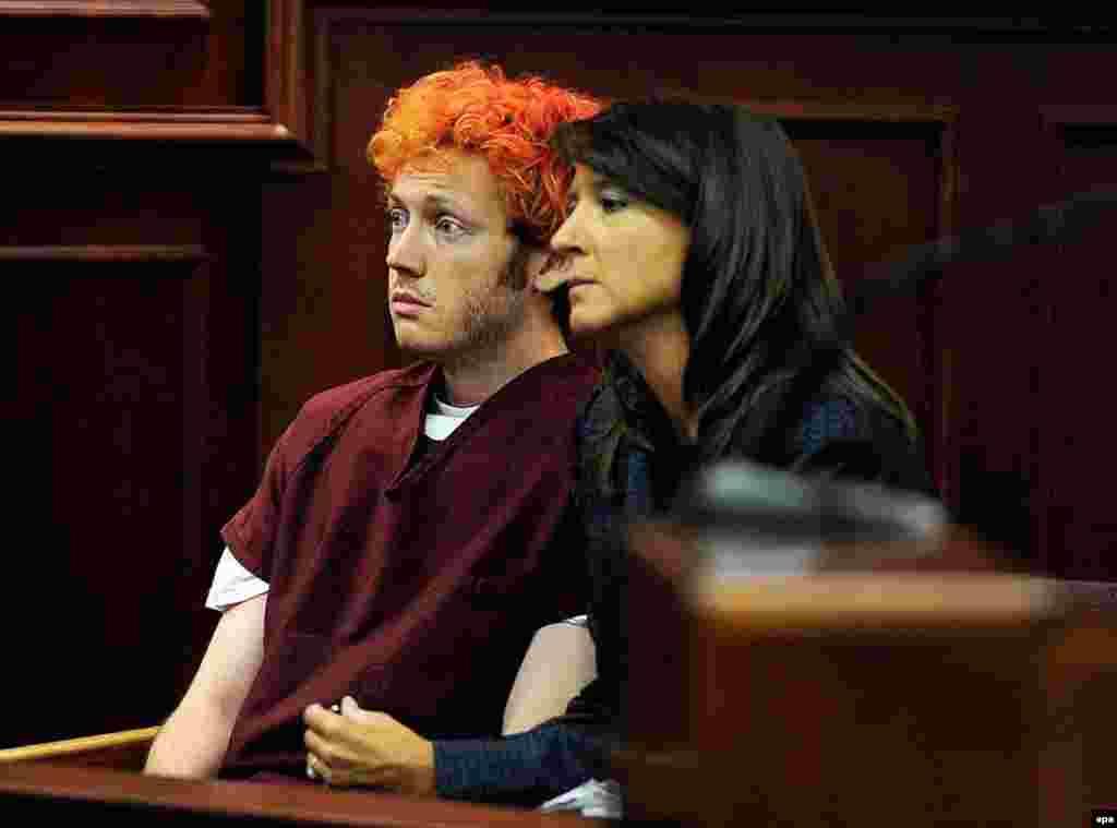 """На фото – 24-летний Джеймс Холмс, житель городка Орора, в зале суда. 20 июля 2012 года он ворвался в местный кинотеатр на премьеру фильма """"Темный рыцарь: Возрождение легенды"""" и расстрелял посетителей с помощью винтовки, помпового ружья и нескольких пистолетов. В ту ночь погибли 12 человек, 58 получили тяжелые ранения. Нападавший отбывает пожизненное наказание без права на УДО."""