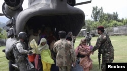 U.S. and Pakistani service members help flood victims exit a U.S. Army helicopter in Khwazakhela
