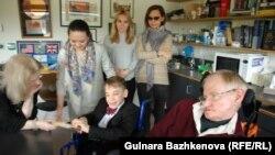 Стивен Хокинг (справа на переднем плане) беседует со школьником из Тараза Исааком Мустопуло после интервью казахстанскому журналисту Гульнаре Бажкеновой (у стены справа). 4 октября 2017 года.
