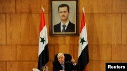 ولید المعلم، وزیر خارجه سوریه زیر عکسی از بشار اسد، رییس جمهوری این کشور.