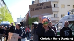 """Demonstrant s transparentom """"Terorizam vakcinacije"""" tokom protesta pristalica teorija zavjere protiv mjera zabrane zbog korona virusa u Berlinu, 18. aprila 2020. godine."""