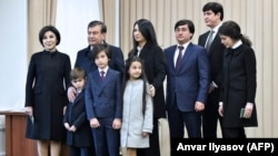Shavkat Mirziyoev (second from left) poses for photographers with his family, including daughter Saida (center top), at a polling station after voting in Tashkent in December 2016.