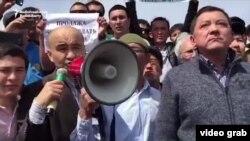 Гражданский активист Макс Бокаев выступает на митинге протеста. Слева от него — аким Атырауской области Нурлан Ногаев. Атырау, 24 апреля 2016 года.