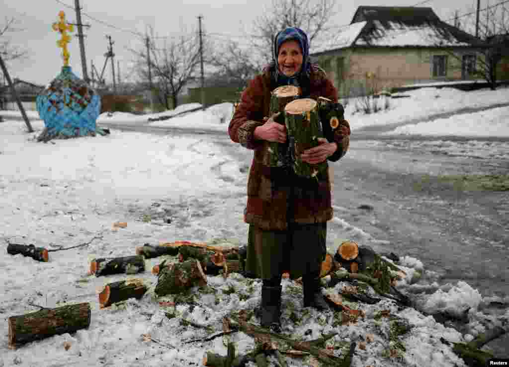 An elderly Ukrainian woman carries firewood for heating her home in the government-held industrial town of Avdiyivka in the war-torn Donbas region. (Reuters/Gleb Garanich)