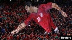 """Египеттің """"Әл-Ахли"""" футбол командасының фанаттары кезекті матч кезінде команданың бұрынғы ойыншысы Мохаммед Абутриканың 3D форматындағы суретін ұстап тұр."""