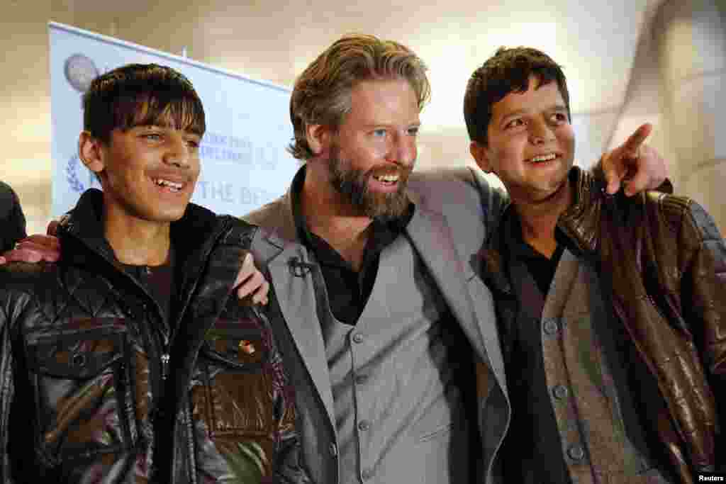 "Director Sam French (center) and 14-year-old Afghan actors Fawad Mohammadi (left) and Jawanmard Paiz of the Oscar-nominated live-action short film ""Buzkashi Boys"" smile for the cameras after arriving at Los Angeles International Airport. (Reuters/Patrick Fallon)"