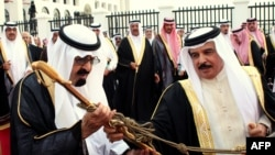 Bahrain's King Hamad bin Issa al-Khalifa (right) giving a sword to his Saudi counterpart, King Abdullah bin Abdul Aziz al-Saud, in Manama on April 18.