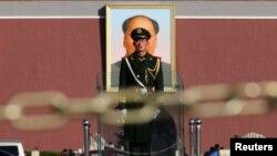 Пекиндегі Тяньаньмэнь алаңындағы Қытайдың бұрынғы басшысы Мао Цзэдунның үлкен суреті қасында тұрған қытай сарбазы. 12 қараша 2013 жыл. (Көрнекі сурет)