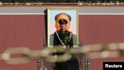 Служащий китайской армии на посту у портрета Мао Цзедуна на площади Тяньаньмэнь в Пекине.
