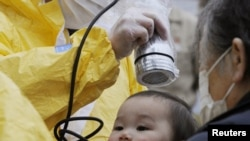 A baby is tested for radiation in Nihonmatsu, Fukushima Prefecture, on March 15.