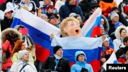Fans hold Russian flags as they watch a skiing competition at the 2014 Winter Olympics in Sochi, Russia.