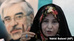 Zahra Rahnavard, wife of the leading reformist presidential candidate Mir Hossein Moussavi (shown in poster), speaks with media in a press conference in Tehran, Iran, Sunday, June 7, 2009.