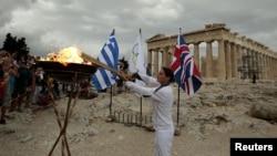 Грецька спортсменка Нікі Ліосі запалює факел від Олімпійського вогню на Акрополі в Афінах, 17 травня 2012 року. Цей факел передадуть британській делегації