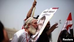 """Musulman doganlygy"" hereketinden prezidentlige kandidat Mohamed Morsiniň tarapdary onuň suratyny ogşaýar, Kair, 18-nji iýun."