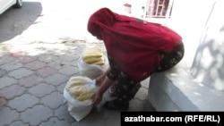 Turkmenistan. Turkmen woman selling corn. National clothes. Ashgabat. June 26, 2014