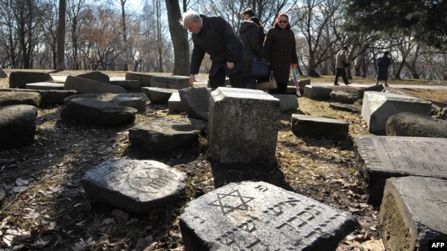 People visit a destroyed Jewish cemetery in March near a memorial to Jews killed in Minsk's Jewish ghetto during the Nazi occupation.