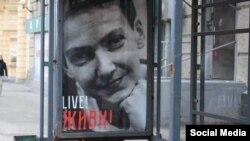 Плакат на автобусной остановке в Москве с изображением Надежды Савченко и надписью: «Live! Живи!» 8 марта 2016 года.