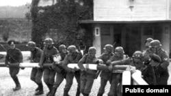 Тарыхый сүрөт: немец аскерлери 1939-жылдын 1-сентябрында Польшанын түндүгүндөгү Сопот шаарындагы чек ара тосмосун талкалап жаткан учур