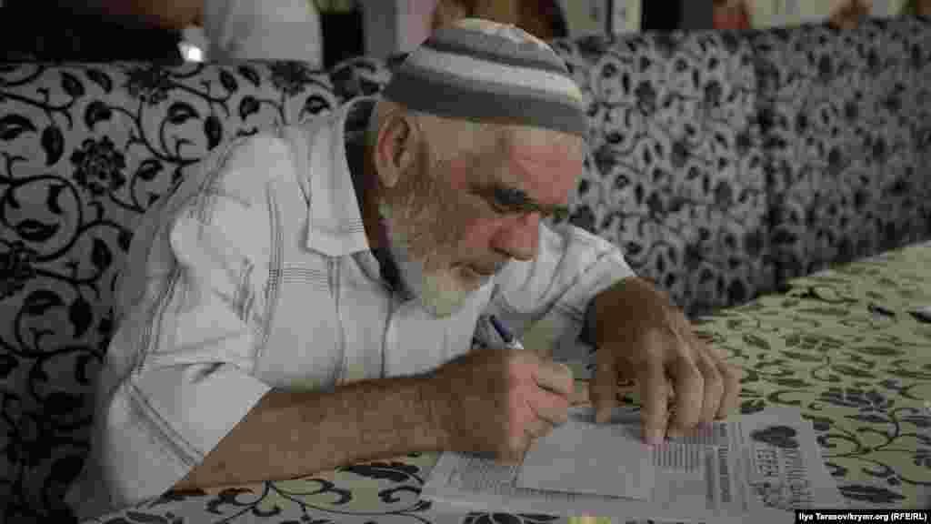 Пожилой активист пишет письмо политзаключенному